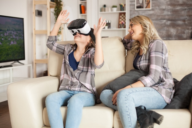 Menina espantada sentada ao lado de sua mãe no sofá enquanto usa um fone de ouvido de realidade virtual.