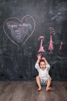 Menina espantada sentado perto de inscrição feliz dia das mães