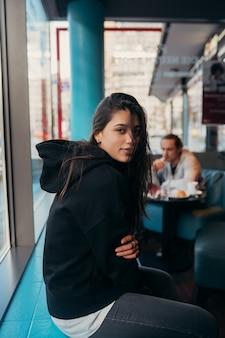 Menina esperando alguém que está atrasado, olhando pela janela