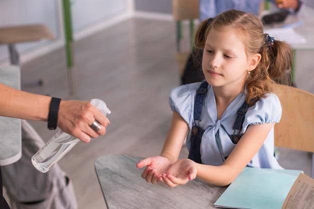 Menina esperando para desinfetar as mãos na sala de aula