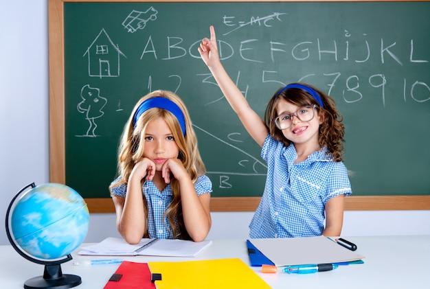 Menina esperta do estudante do lerdo na sala de aula que levanta a mão