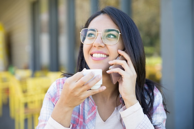 Menina esperta positiva do estudante que aprecia a conversa agradável do telefone