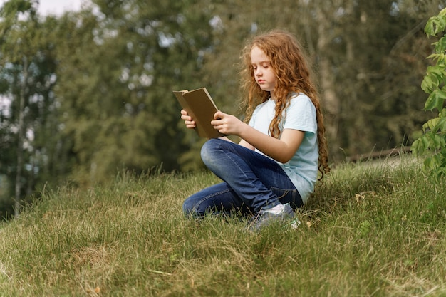 Menina esperta que lê o livro ao ar livre.