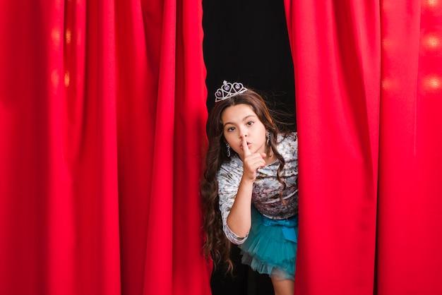Menina espiando da cortina vermelha fazendo gesto silencioso