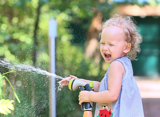 Menina espirra alegremente a água de uma mangueira de rega em um dia ensolarado de verão.