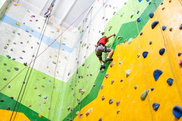 Menina esportiva escalando pedra artificial em uma parede prática no ginásio
