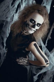Menina esqueleto bruxa posando nas teias, halloween. a bruxa está se preparando para as noites de férias dos mortos