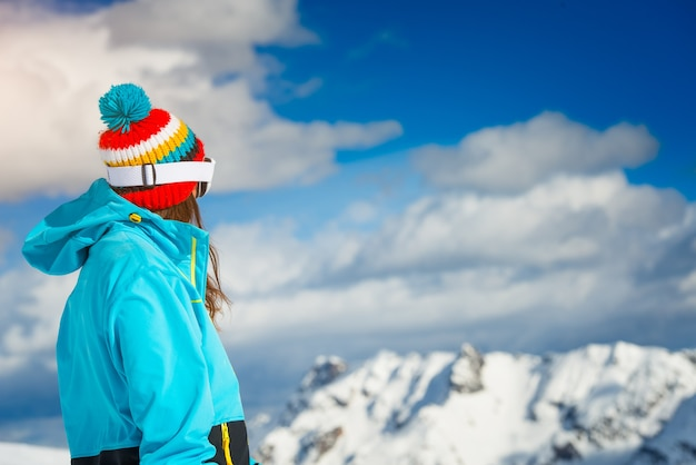 Menina esquiadora de freeride olhando para as montanhas distantes