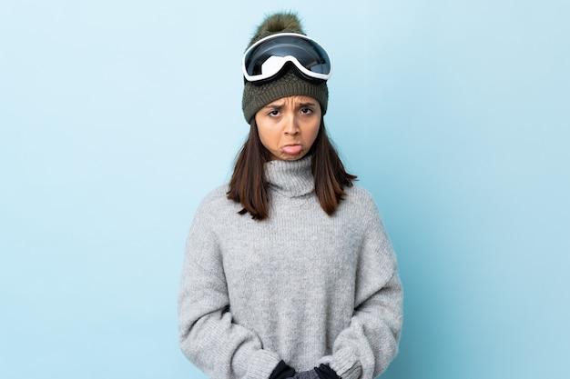 Menina esquiadora de raça mista com óculos de snowboard sobre fundo azul isolado com expressão triste.