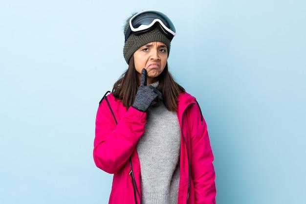 Menina esquiadora de raça mista com óculos de snowboard sobre parede azul isolada, tendo dúvidas enquanto olha para cima.