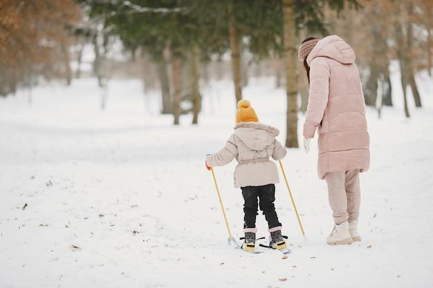 Menina esquiando com a mãe