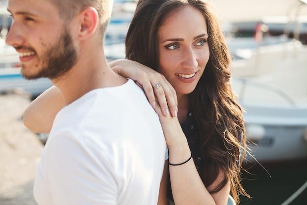 Menina está abraçando o noivo no iate no cais.