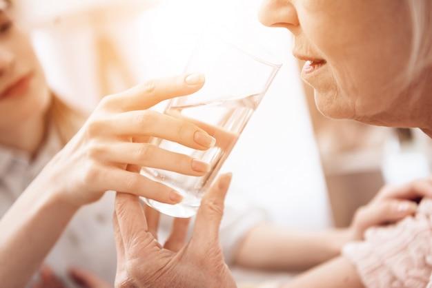 Menina está ajudando a mulher com um copo de água.