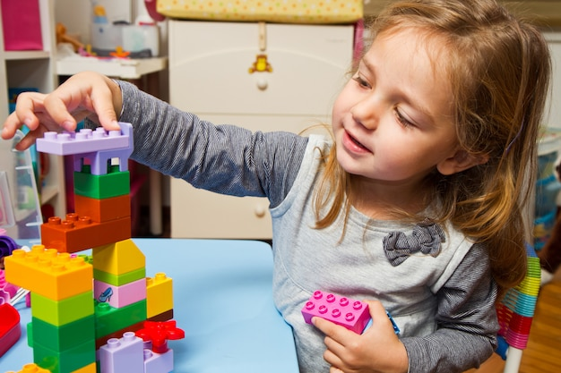 Menina está brincando com tijolos de construção