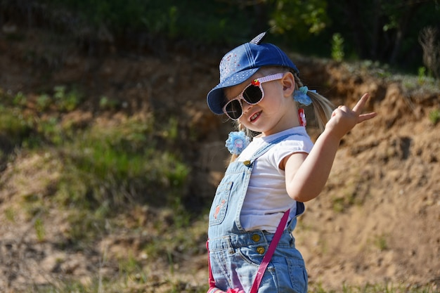 Menina está brincando e rindo no gramado verde no verão