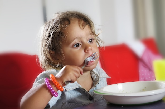 Menina está comendo com um garfo