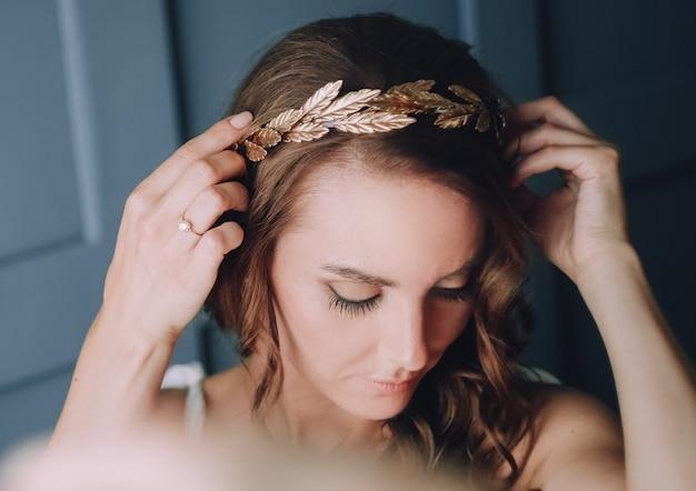 Menina está consertando na cabeça dela um aro dourado com folhas de louro