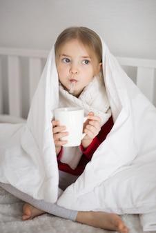 Menina está doente, segurando um termômetro na mão, debaixo do cobertor, olhos tristes, vírus