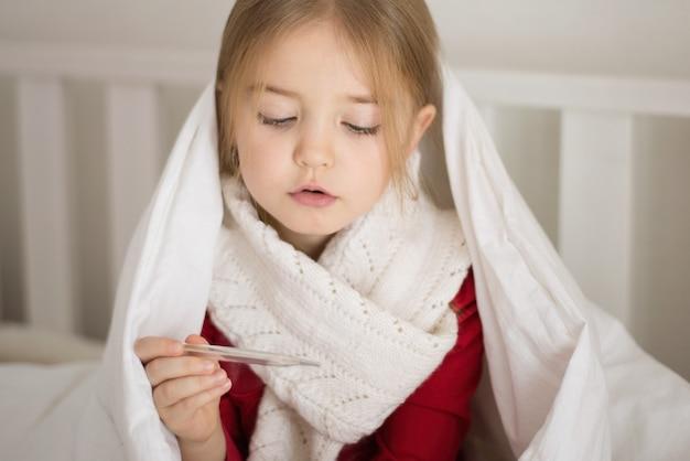 Menina está doente, segurando um termômetro na mão