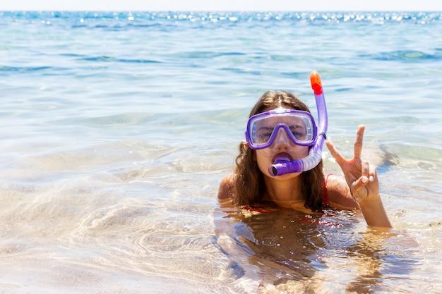 Menina está envolvida em mergulho em um mar limpo e claro.