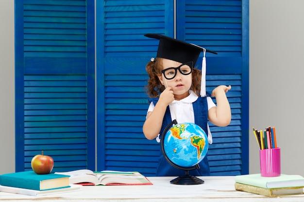 Menina está estudando enquanto usava um chapéu de formatura