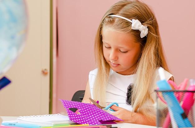 Menina está fazendo artesanato de feltro. ocupação criativa para crianças. copie o espaço