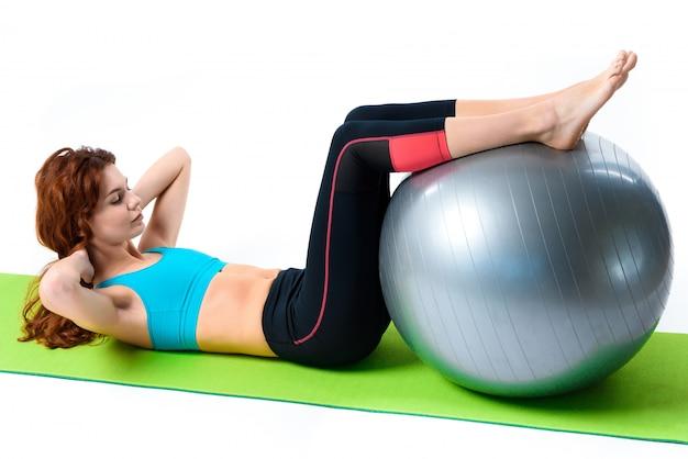 Menina está fazendo exercícios crunch com bola de ginástica.