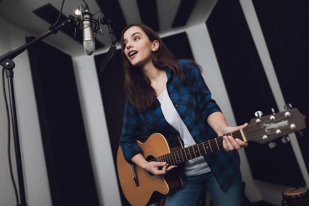 Menina está gravando uma música em um estúdio de gravação moderno.