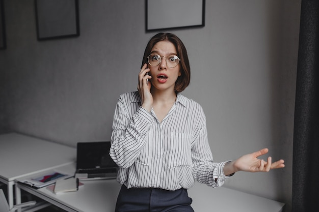 Menina está indignadamente falando no telefone, olhando para a câmera no fundo da área de trabalho branca e laptop.