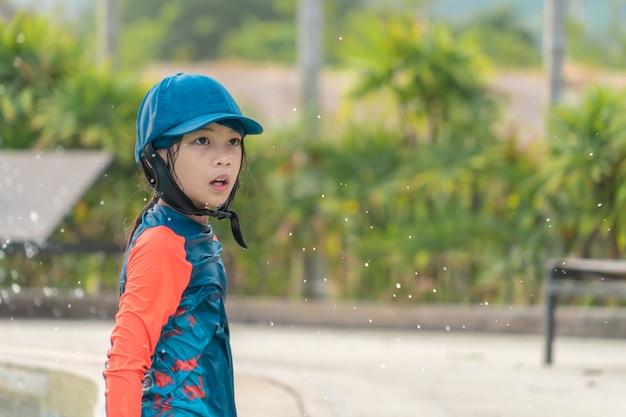 Menina está jogando na piscina de treinamento de natação