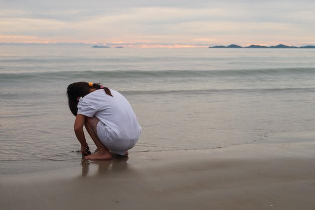 Menina está jogando no litoral de costa de praia de areia para imaginação e mediação e conceito de auto-aprendizagem ao ar livre com espaço de cópia