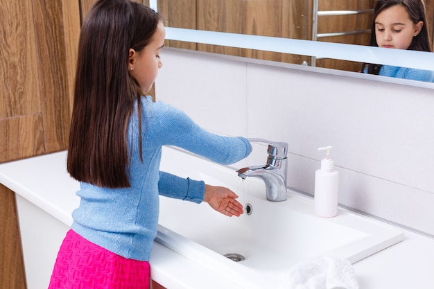 Menina está lavando as mãos no banheiro