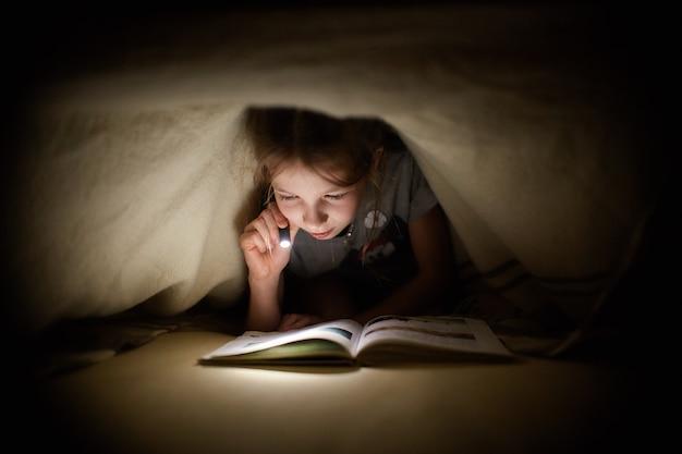 Menina está lendo um livro debaixo de um cobertor com uma lanterna em um quarto escuro à noite