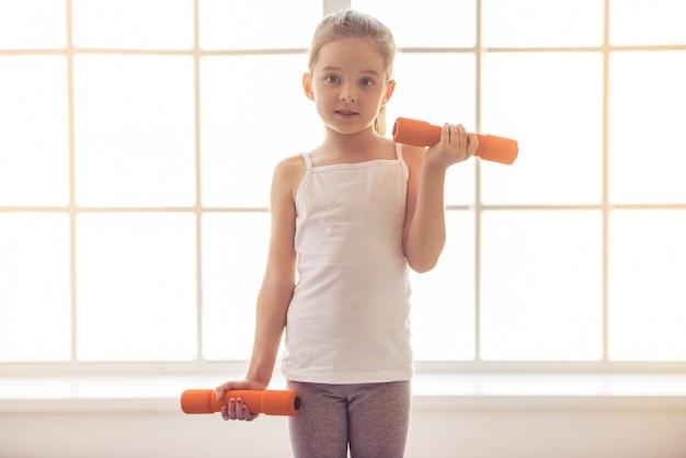 Menina está malhando com halteres na sala de fitness