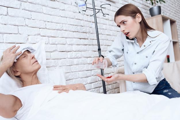 Menina está no telefone, dando pílulas para mulher.
