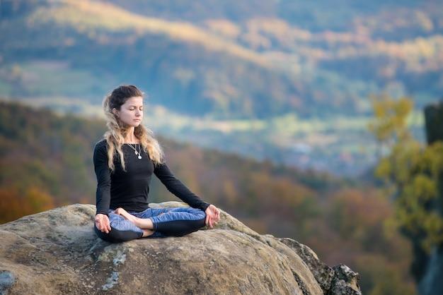 Menina está praticando ioga e fazendo asana siddhasana no topo da montanha