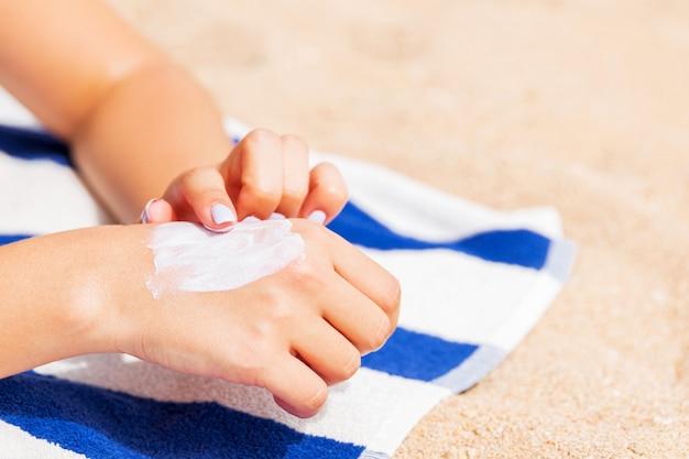 Menina está relaxando na toalha na areia da praia e aplicando protetor solar na mão.