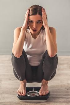 Menina está segurando a cabeça enquanto agachando-se em balanças de peso.