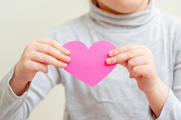 Menina está segurando coração rosa
