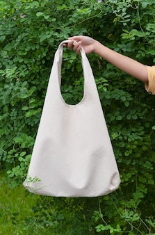Menina está segurando o saco de lona