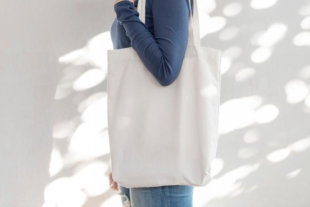 Menina está segurando o tecido da lona do saco para o modelo em branco de maquete isolado no fundo de luz e sombra.