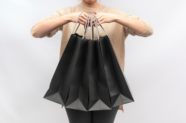 Menina está segurando sacolas de papel preto. saco de papel.