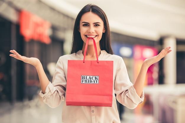 Menina está segurando uma sacola de compras com a frase