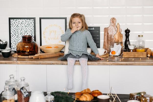 Menina está sentada na mesa da cozinha.