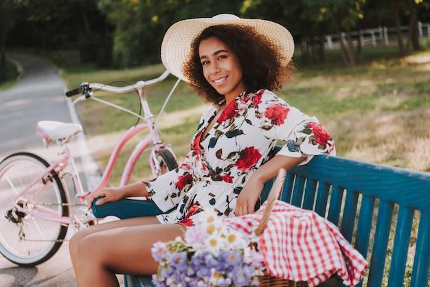 Menina está sentada no banco do parque ao lado da bicicleta.