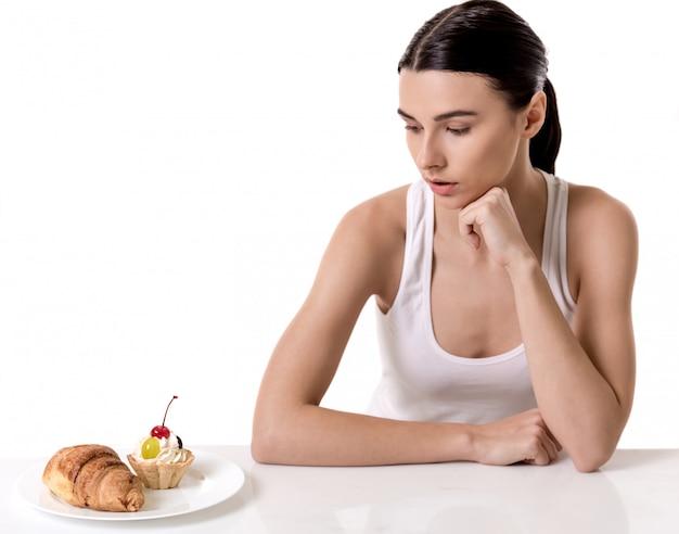 Menina está sentada perto do prato com doce e olhando para ele