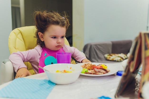 Menina está tomando café da manhã enquanto assiste o filme sobre o tablet.