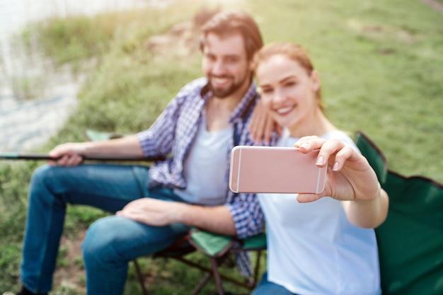 Menina está tomando selfie de si mesma e seu marido. eles estão olhando para o telefone e sorrindo. cara está segurando o fim da vara de peixe. as pessoas estão sentadas em cadeiras dobráveis.