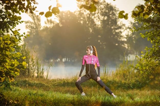 Menina, estendendo-se com os olhos fechados e se preparando para correr na manhã ensolarada, perto do lago