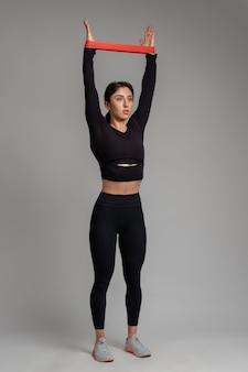 Menina esticando a faixa de resistência nos braços acima da cabeça na parede cinza